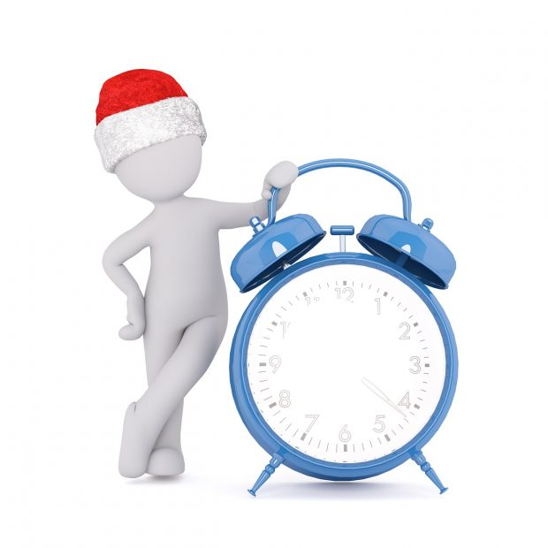 Man with Santa hat relaxing by clock